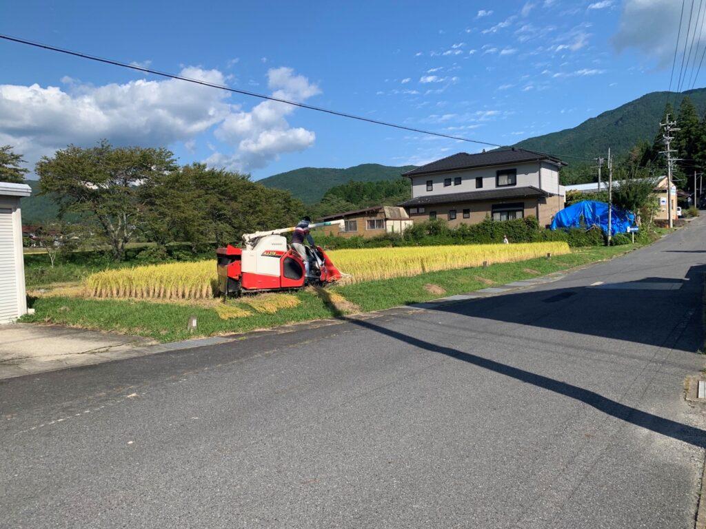 恵那三洋製作所の近くで稲刈りをしている光景